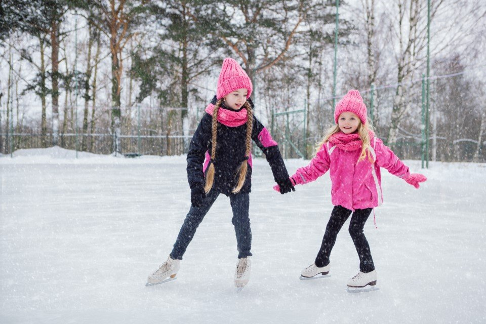 Young sisters with long blond hair ice skating outdoors