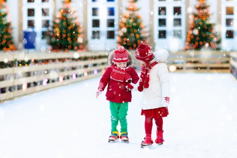 Little girl helping her younger brother skate