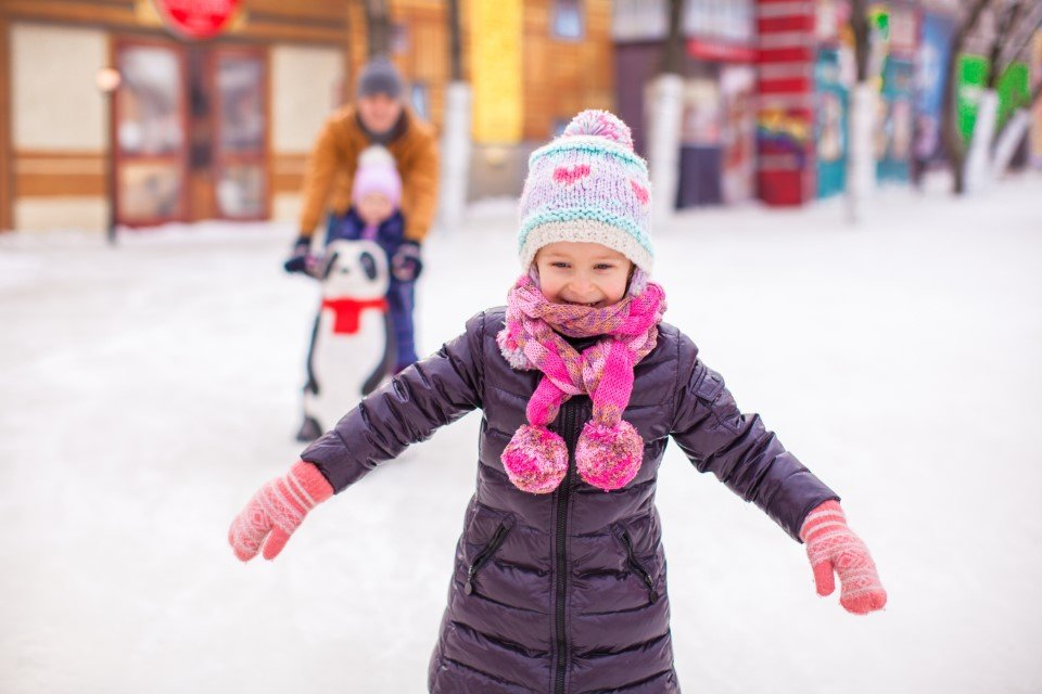 Happy little girl at an outdoor ice rink