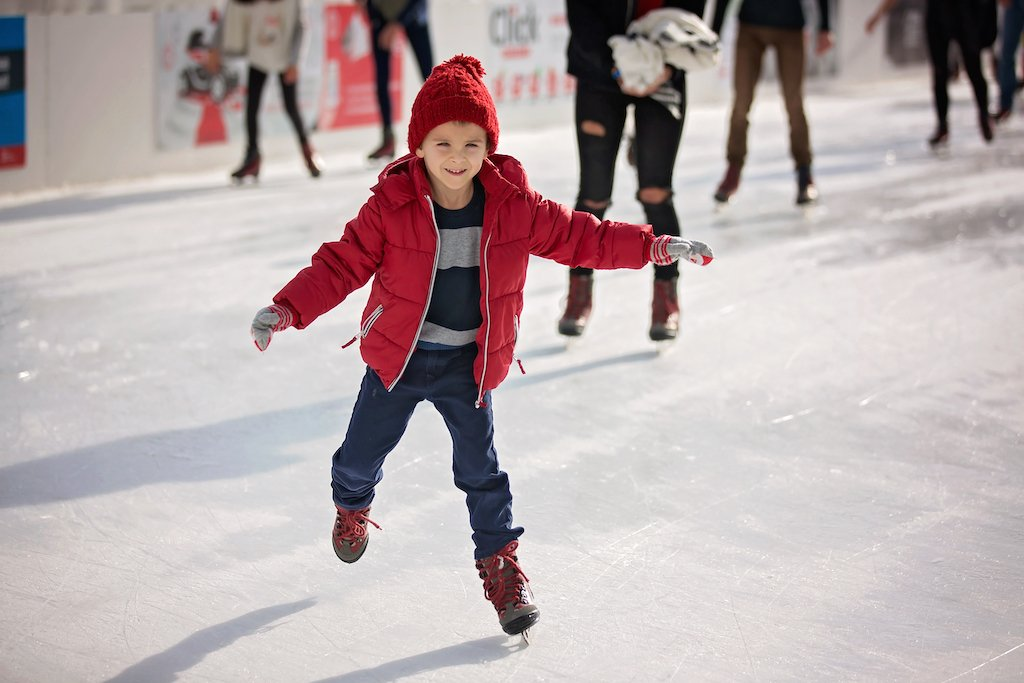 A boy skating on a real outdoor ice rink