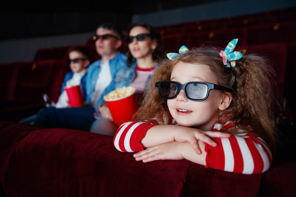 Girl with pony tails at the cinema with her family