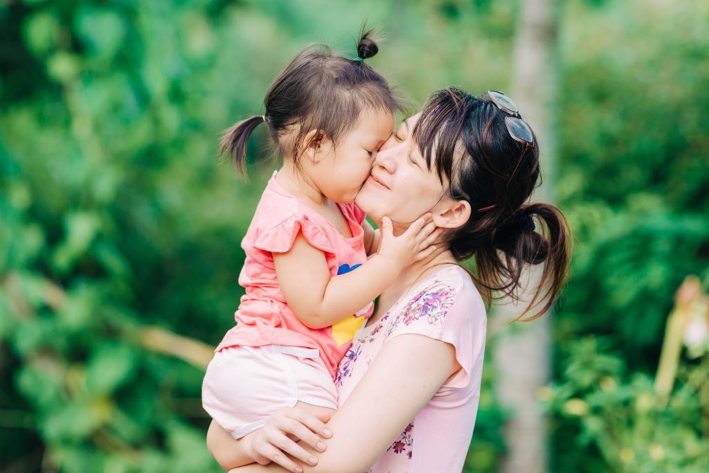 Mum and baby girl kiss