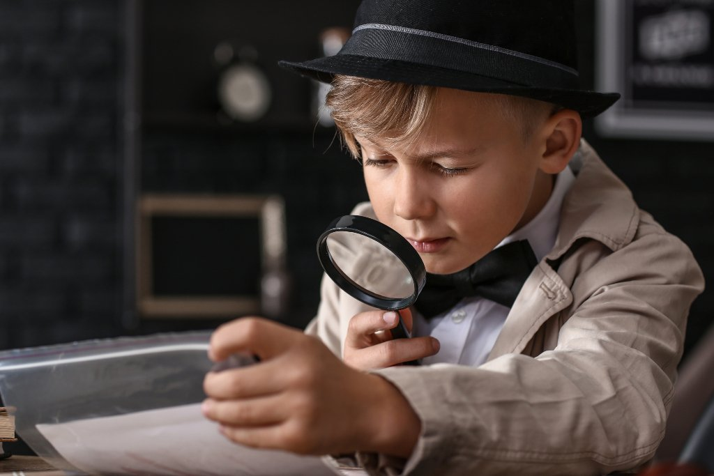 Boy with magnifying glass solving clues