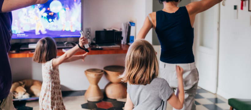 A family doing a dance workout in their living room